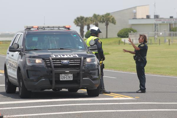 Corpus Christi police officers block the intersection of Ocean Drive and Sand Dollar Boulevard Thursday afternoon after a shooter stormed the north gate of the Naval Air Station Corpus Christi around 6:15 a.m.