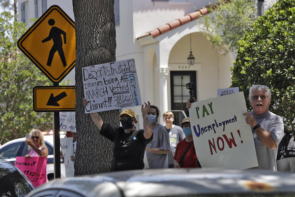 Protestors wave signs at Gov. Ron DeSantis as he and Vice President Mike Pence visit  Orlando on May 20, 2020. DeSantis has called the state's unemployment filing system a jalopy while defending his efforts to fix it.