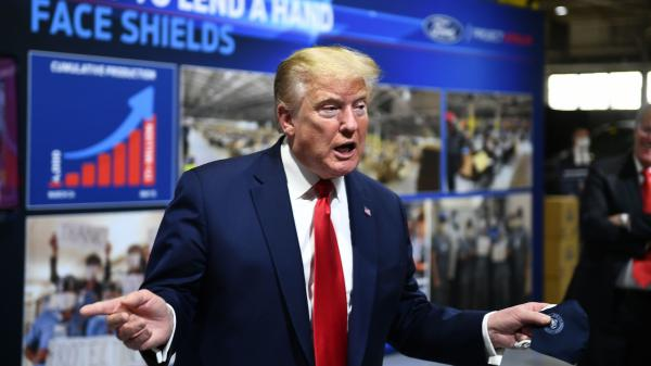 President Trump holds a mask as he speaks during a tour of the Ford Rawsonville Plant in Ypsilanti, Mich., on Thursday.