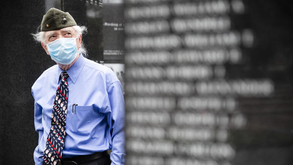 A U.S. Marine Corps veteran pays his respects at the Korean War Memorial behind a face mask in Philadelphia.