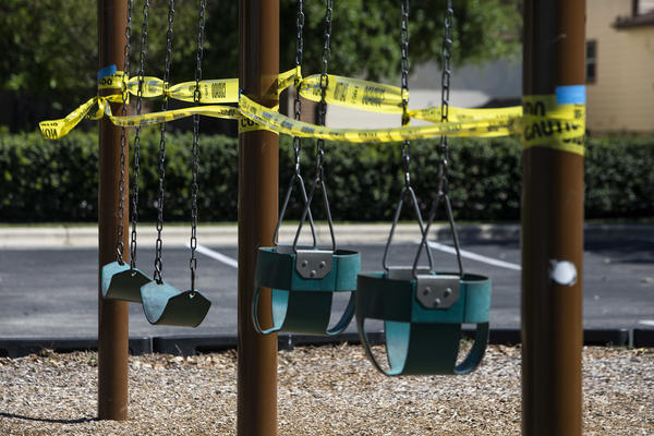 Caution tape surrounds playground and park equipment closed at the McKinney Heights Park in South Austin during the coronavirus pandemic.
