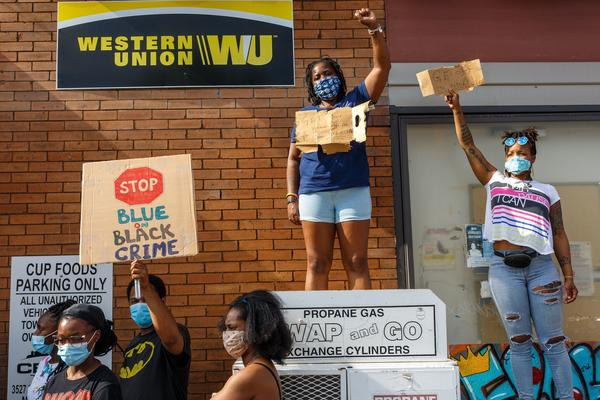 """Women hold signs while protesting near the area where a Minneapolis Police Department officer allegedly killed George Floyd, on Tuesday in Minneapolis, Minn. A 10-minute <a href=""""https://www.facebook.com/darnellareallprettymarie/videos/1425398217661280/"""">video widely circulated on social media</a>  shows a police officer using his knee to pin the man's neck to the ground for multiple minutes."""