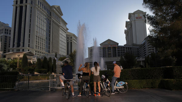 Cyclists stop to look at the fountains at the Caesars Palace hotel and casino on Tuesday on the Las Vegas Strip, which is empty of its normal crowds because of the COVID-19 pandemic.