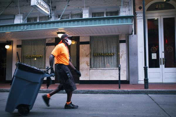 A worker hauls trash outside Galatoire's in the French Quater. New Orleans, Louisiana. May 26, 2020.