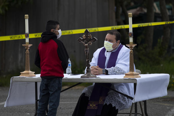 Father Jose Alvarez, right, during walk and drive through confessions on Friday, April 24, 2020, in the parking lot at Holy Family Roman Catholic Church in White Center.