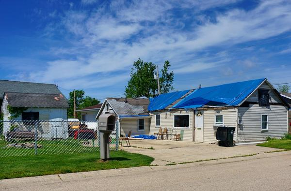 There are occupied homes that still have tarps covering their roofs a year after the tornado outbreak.