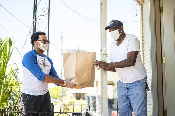 Jose Fermin Ceballos from the Krewe of Red Beans delivers produce and grocery items to Benny Jones, a local drummer and the leader of the Treme Brass Band, as a part of their Feed The Second Line fundraising effort.