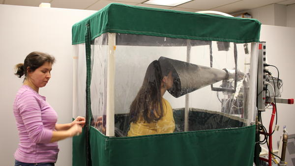 """Undergraduate Shira Rubin gamely demonstrates the Gesundheit machine, which collects samples of virus from the breath that sick students exhale. Rubin helps <a href=""""https://gotflu.umd.edu/people.html#syoussefi"""">Dr. Somayeh Youssefi</a> (left) set up the machine before patients use it."""