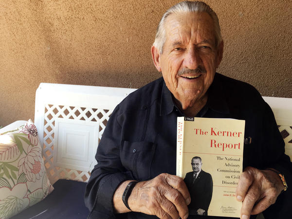 Former Democratic Sen. Fred Harris of Oklahoma, seen in August 2017, holds a copy of The Kerner Report, as he discusses its 50th anniversary. Harris is the last surviving member of the Kerner Commission.