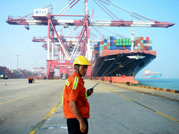 A Chinese worker looks on as a cargo ship is loaded at a port in Qingdao, in eastern China's Shandong province, in July 2017. The United States is China's biggest single export market.