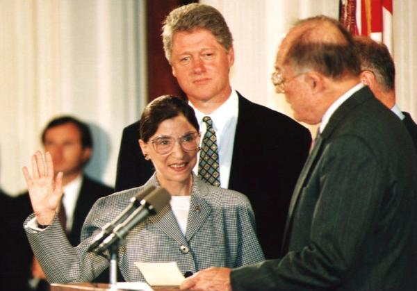 U.S. Supreme Court Justice Ruth Bader Ginsburg (left) takes the oath of office in August 1993 as President Bill Clinton looks on. A new album, <em>Notorious RBG in Song</em> sets events from Ginsburg's life to music.