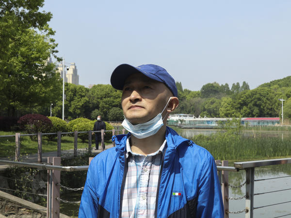 "Zhang Hai stands on a bridge where he took his father out for a walk only about four months earlier. His father died of the novel coronavirus on Feb. 1. ""The scenery is still here, but the person is gone,"" he sighs. He says he frequently comes to this park ""looking for memories."""