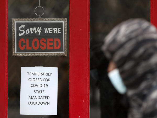 A pedestrian walks by a closed shop in Grosse Pointe, Mich., on Thursday. The Labor Department is expected to report on Friday that the U.S. lost millions of jobs last month because of the coronavirus pandemic.
