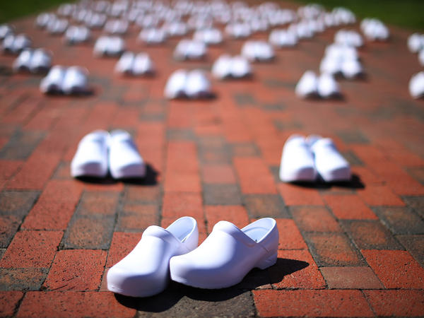 As part of a demonstration across from the White House on May 7, National Nurses United set out empty shoes for nurses who have died from COVID-19. The union is asking employers and the government to provide safe workplaces, including adequate staffing. Hospitals have been laying off and furloughing nurses due to lost revenue.