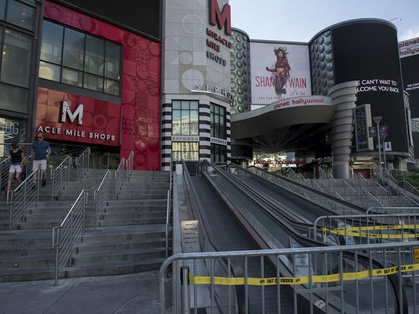 People walk near closed shops on a quiet Las Vegas Strip on May 8. Retail sales dropped a record 16.4% last month.