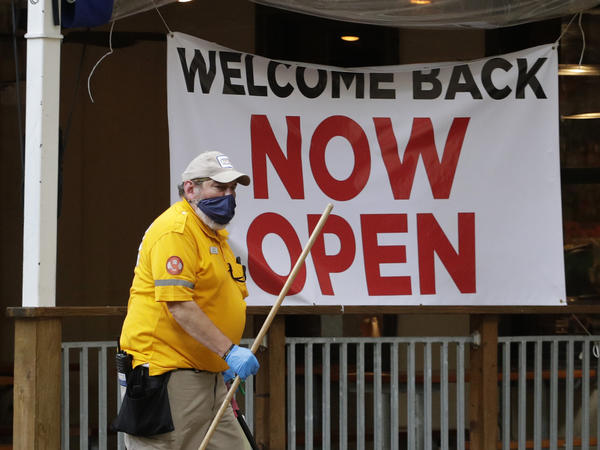 A worker passes a sign at a restaurant along San Antonio's River Walk that has reopened. As businesses reopen around the U.S., many workers are worried for their health.