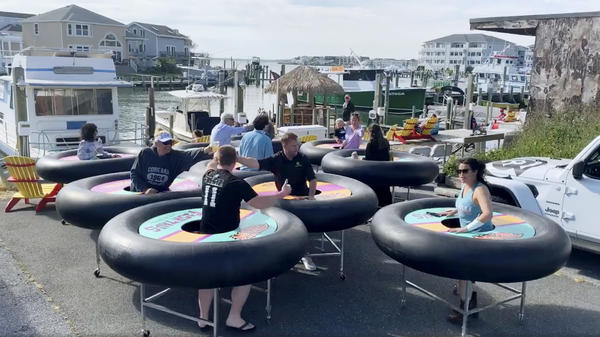 """Fish Tales Bar & Grill, a restaurant in Ocean City, Md., tries out """"bumper tables."""" Designed by an event production company, they're meant to allow diners to practice social distancing."""