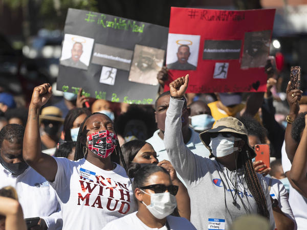 People react during a rally to protest the shooting of Ahmaud Arbery in Brunswick, Ga.