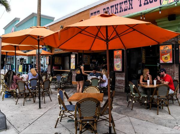 People eat outside of a restaurant in Fort Lauderdale, Fla., on May 18.
