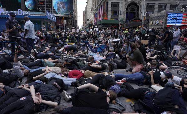 Protesters lie on the ground with their hands behind their backs in New York City's Times Square on Monday. Outrage over police brutality and systemic racism has spilled into the streets in cities across the country.
