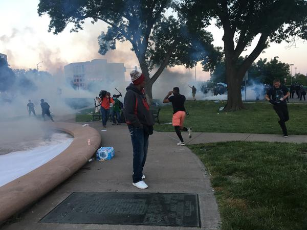 Police deploy tear gas to disperse demonstrators at Mill Creek Park shortly after the 8 p.m. curfew took effect.