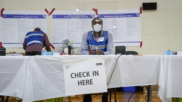 An election official waits to check in voters behind a plastic barrier Tuesday at a polling place at McKinley Technology High School in Washington, D.C.