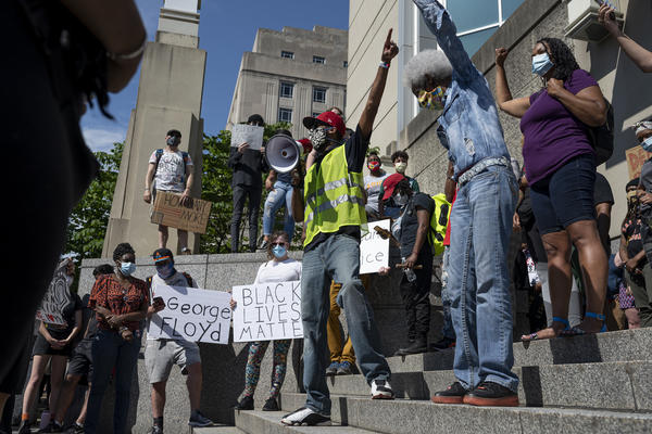 Protesters listened to speakers on the steps of the City Justice Center on Monday.
