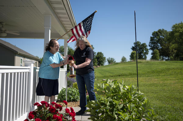 LuAnn Cooper, right, helps her client Margie refill the bird feeder in front of her home in Washington, Missouri. Cooper has worked as an in-home caregiver for people with developmental disabilities for more than two years.