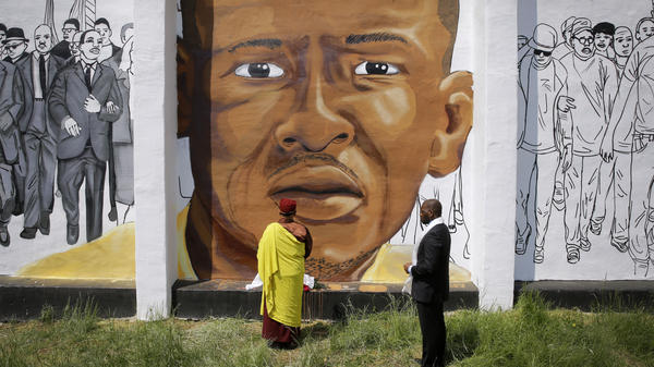 Faith leaders stand before a Baltimore mural depicting Freddie Gray, who died April 19, 2015 of injuries sustained while in police custody.