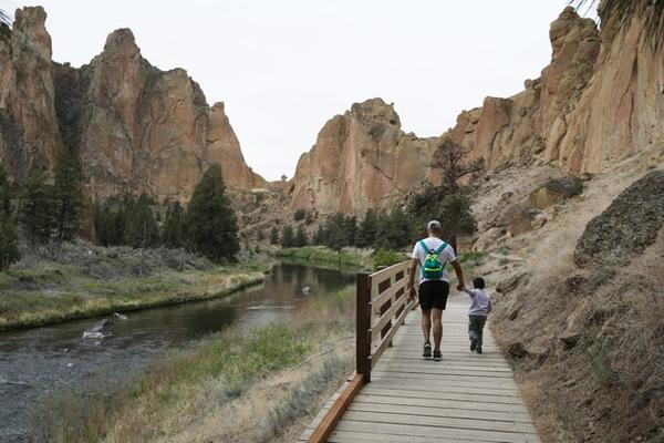 <p>A man walks&nbsp;hand-in-hand with a small boy in Smith Rock State Park on May 16, 2020.&nbsp;</p>