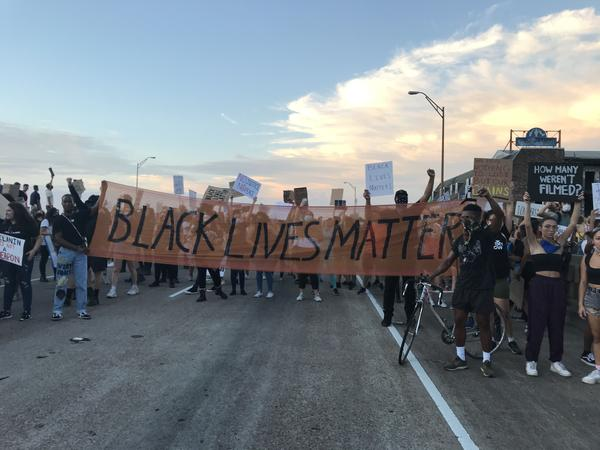 Hundreds of protestors march on the interstate, halting traffic.
