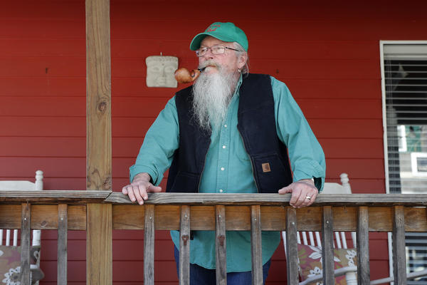 Mayor Phil Stang stands on the front porch of his home in Kimmswick, Mo., on April 7. The tiny town along the banks of the Mississippi River, normally bustling with out-of-town visitors this time of year, is virtually empty as the economic ravages of the coronavirus have shuttered shops and restaurants in the community.
