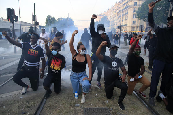 Protesters on Tuesday in Paris take a knee, as riot officers fire tear gas and scattered protesters throw projectiles and set fires at an unauthorized demonstration against police violence and racial injustice. Several thousand people rallied peacefully for two hours around the main Paris courthouse in tribute to George Floyd and to Adama Traoré, a French black man who died in police custody.