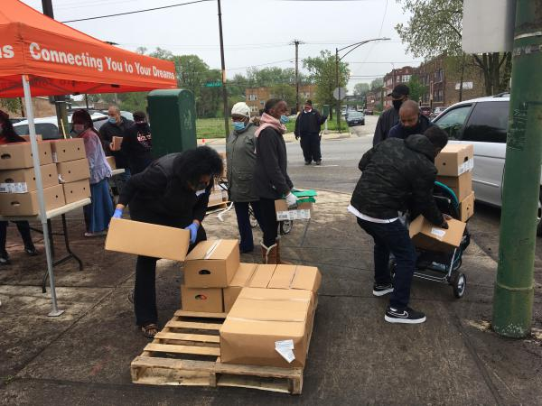 Residents of the Auburn Gresham neighborhood in Chicago line up for boxes of food at a weekly pop-up food pantry.