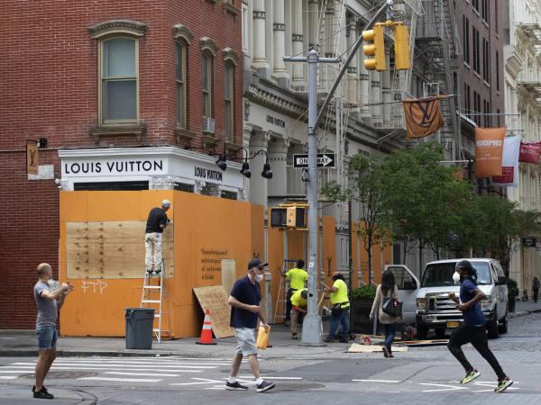 Workers board up windows of a store in the SoHo neighborhood of New York City, where some nonessential businesses are allowed to reopen starting Monday after an almost three-month lockdown because of the coronavirus pandemic.