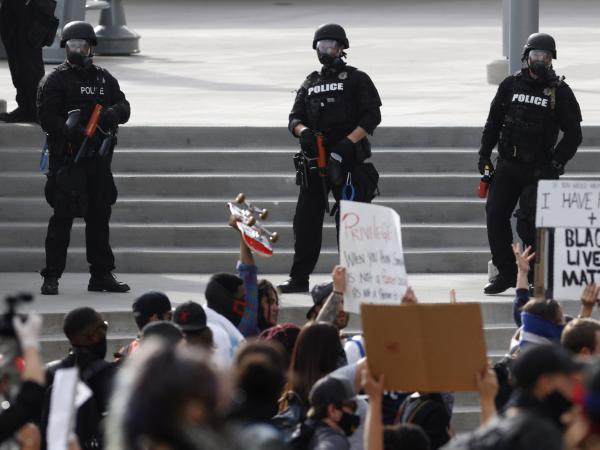 Denver Police observe the crowd during a protest outside the State Capitol on Saturday, May 30, 2020, in Denver.