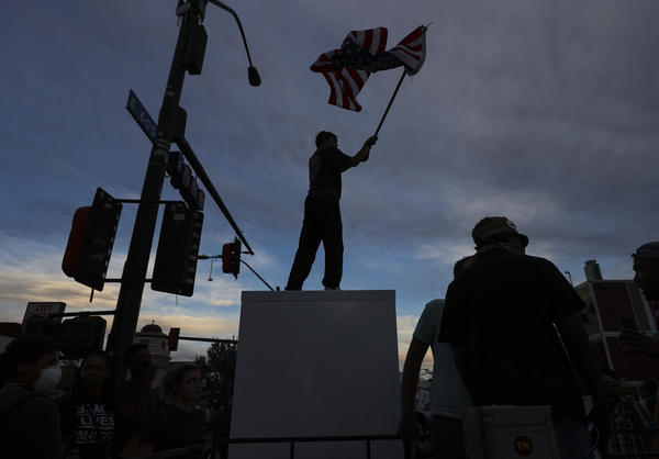 A protester waves an upside down U.S. flag the death of George Floyd in downtown Las Vegas on Saturday, May 30, 2020.