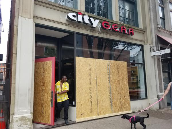 A customer exits City Gear, which sustained damage during weekend protests but is open for business.
