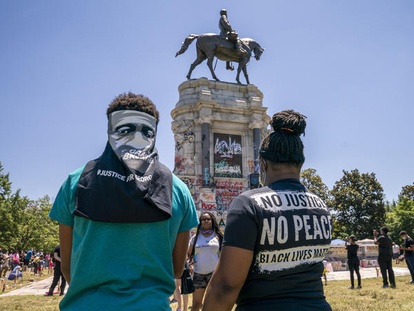 People gather at the Robert E. Lee Monument, now covered by protest graffiti, in Richmond, Va., on Sunday. A judge on Monday issued a temporary injunction against its removal.