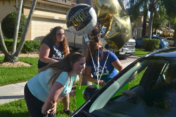Annabel Claprood, her mom, Elyse, and her sister, Macy, talk to a family friend through a car window during a surprise graduation parade.