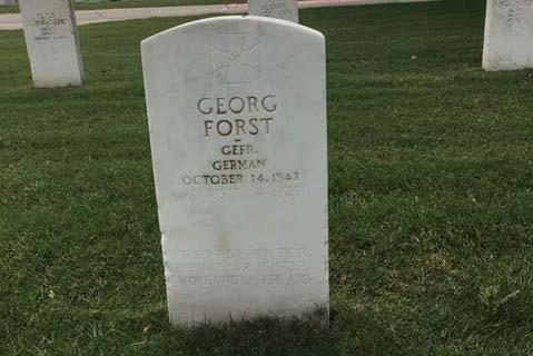 A gravestone for a German POW in the San Antonio VA cemetery. The stone is engraved with a swastika and an inscription that references Adolf Hitler.