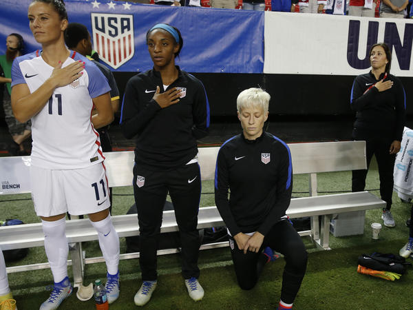 USA's Megan Rapinoe (right), kneels next to teammates Ali Krieger and Crystal Dunn as the national anthem is played before an exhibition soccer match against Netherlands on Sept. 18, 2016, in Atlanta.