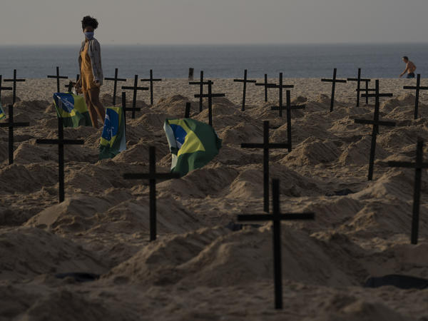 A woman walks amid symbolic graves on Copacabana Beach, dug by activists from the NGO Rio de Paz protesting the government's handling of the COVID-19 pandemic in Rio de Janeiro on Thursday.