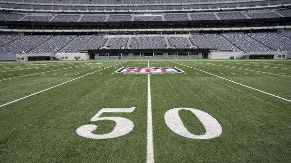 The NFL logo on the 50-yard line at an empty NFL stadium.