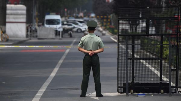 A law enforcement officer stands guard at the entrance of the Xinfadi market Saturday in Beijing. A fresh cluster of coronavirus cases linked to the market prompted officials to institute immediate and sweeping restrictions, including the market's closure.