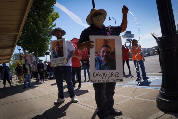 Emmanuel Anguiano-Mendoza, left, and Agustin López hold posters featuring featuring David Cruz, a worker who died on May 30.Enrique Pérez de la Rosa/NWPB