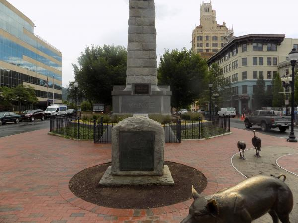 The marker with the likeness of Robert E. Lee in Pack Square in 2017, before it was damaged.  Behind it is the Vance Monument.  A task force will now decide whether to remove the Vance Monument, or recontextualize it