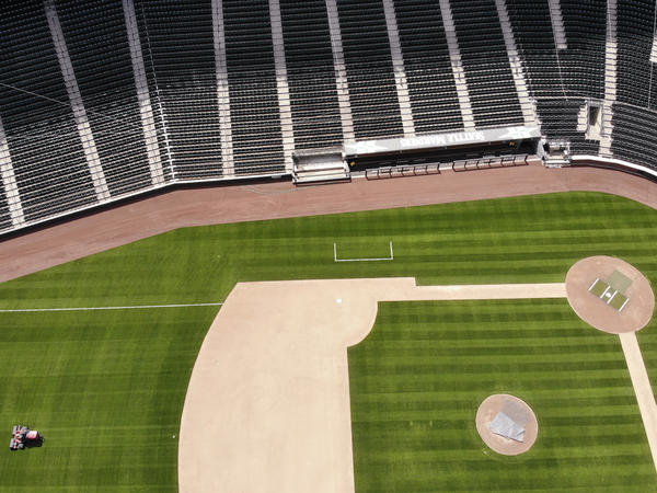 A grounds crew member mowed in right field as work continued to keep the Seattle Mariners' field this May. Now the MLB's season may be in jeopardy.