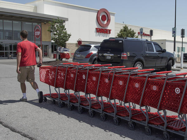 "A Target worker corrals shopping carts in Omaha, Neb., on June 16. The company is making permanent a $2 bonus it created during the pandemic, as many retailers have been phasing out ""hazard pay."""