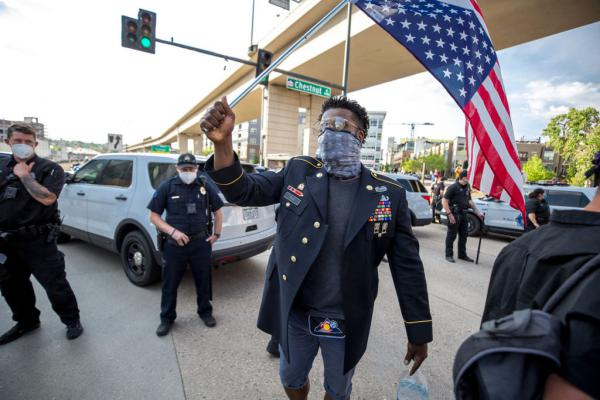 Aubrey Rose, an 18-year U.S. Army veteran, marches with an upside-down American flag over his shoulder in a protest against police violence in Denver.